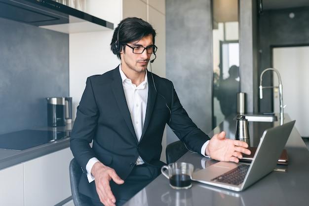 Empresario con auriculares en una videoconferencia desde la computadora de su casa