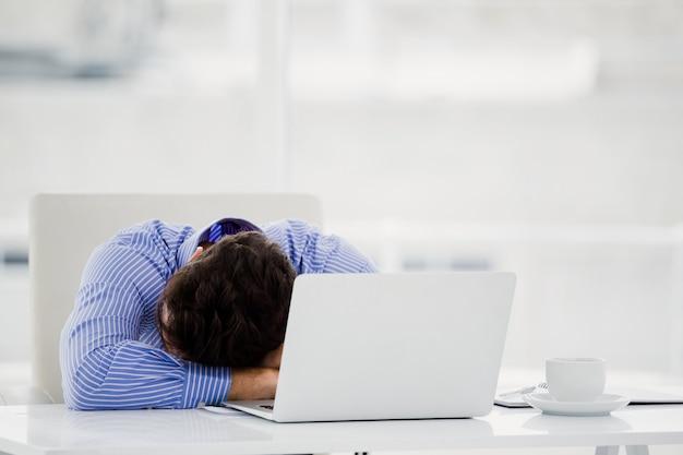 Empresario bajando la cabeza sobre el escritorio