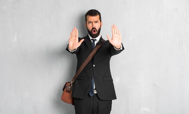 Empresario con barba haciendo gesto de parada para decepcionado con una opinión