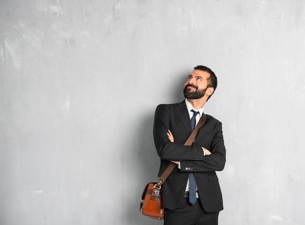 Empresario con barba mirando hacia arriba mientras sonríe