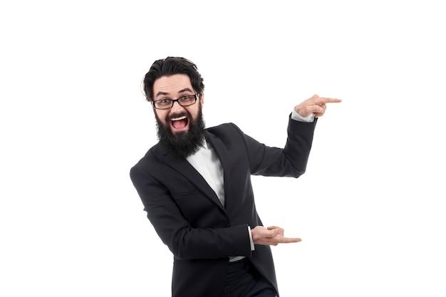Empresario barbudo positivo apuntando hacia el lado, aislado en la pared blanca