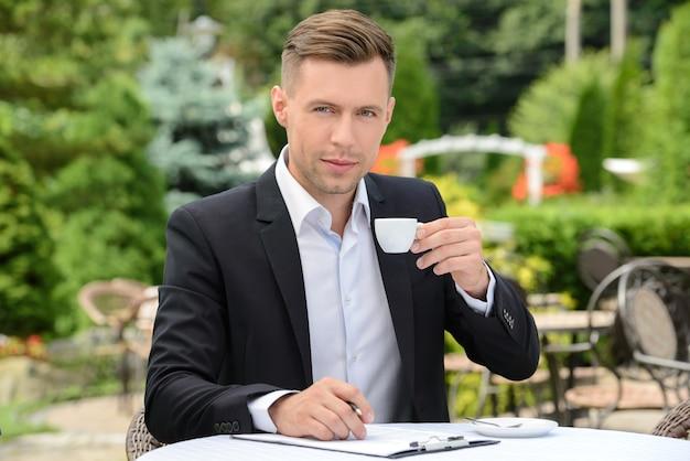 Empresario bebiendo café sentado en un café.