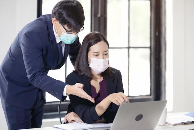 Empresario y bella empresaria sentada en el escritorio en la oficina de coworking con mascarilla debido a covid-19