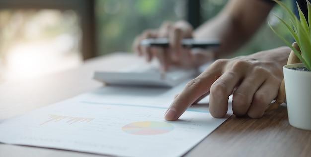Empresario bolígrafo apuntando el volumen de negocios con el informe del gráfico y el uso de una computadora portátil para los datos de análisis
