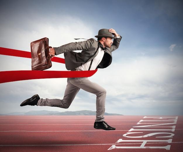 Empresario con bolsa va más allá de la cinta roja a la llegada de una carrera