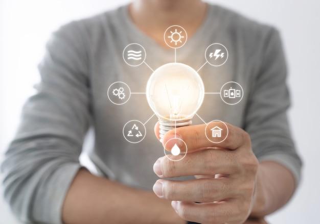 Empresario con bombilla brillante con icono de recursos energéticos