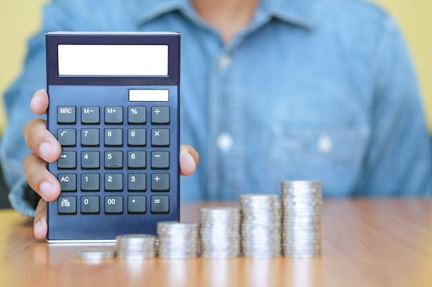 Un empresario con una calculadora y una pila de monedas en primer plano