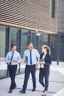 Empresario caminando con colegas fuera del edificio de oficinas