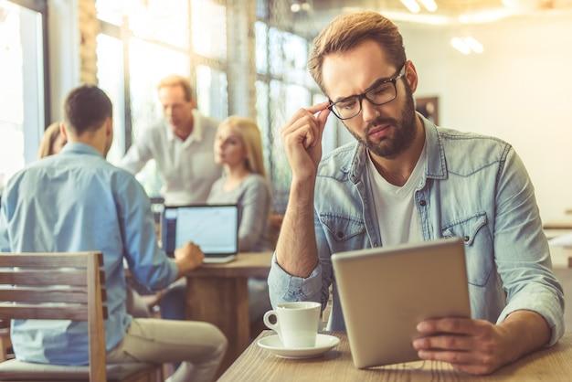 Empresario en camisa y anteojos está utilizando tableta digital.