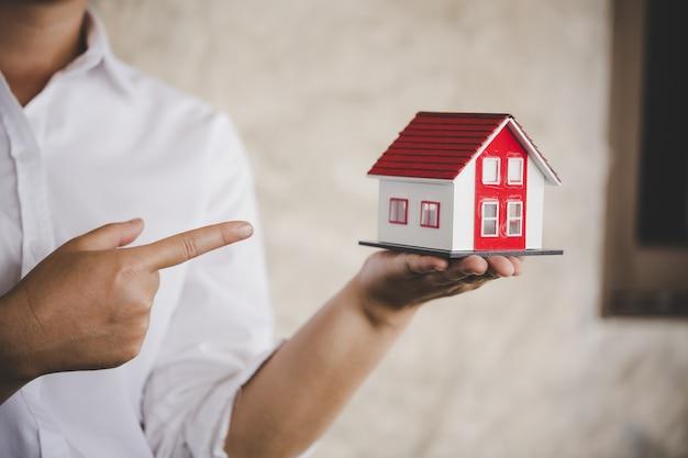 Empresario en camisa blanca sosteniendo una pequeña casa en la mano
