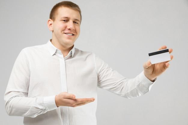 Empresario en camisa blanca con tarjeta bancaria en mano aislado en blanco