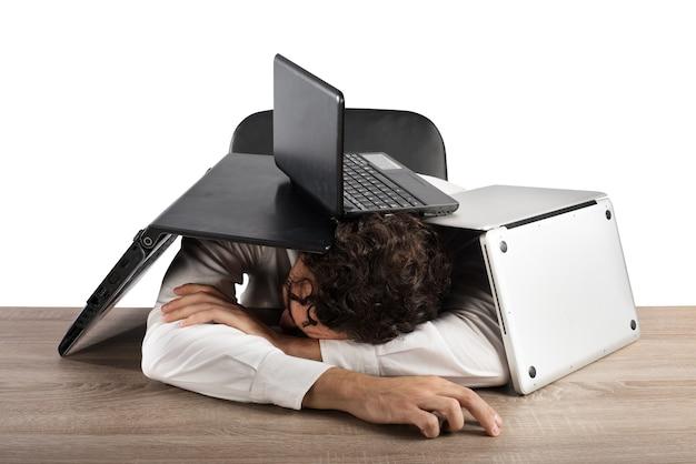 Empresario cansado durmiendo bajo una pila de computadoras