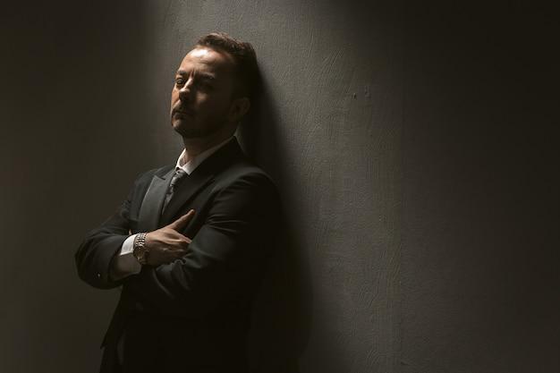 Empresario cansado siente strees. hombre caucásico maduro en traje oscuro con los ojos cerrados con los brazos cruzados sobre fondo de pared oscura