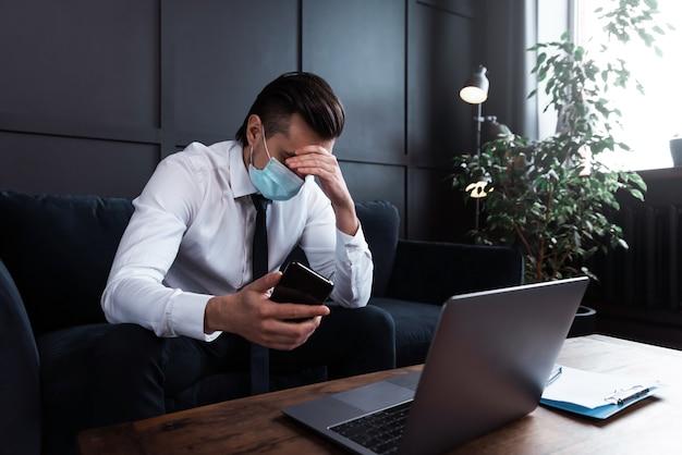 Empresario cansado con síntomas de enfermedad con máscara de prevención durante su trabajo