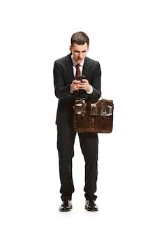 Empresario con carpeta charlando en el teléfono inteligente aislado en la pared blanca