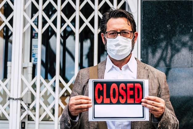 Empresario con cartel de cerrado fuera de su tienda por crisis económica del coronavirus