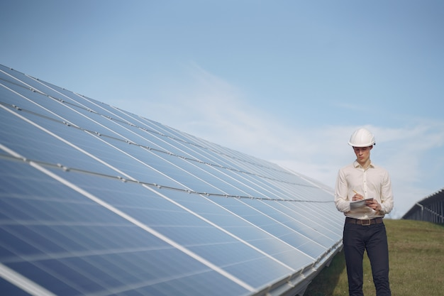 Empresario en un casco blanco cerca de batería solar