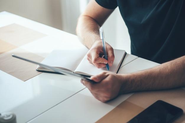 Empresario caucásico escribiendo algo en un libro usando una tableta para copiar
