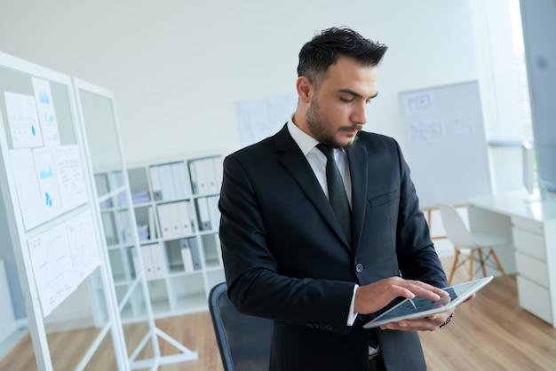Empresario caucásico en traje elegante de pie en la oficina y usando tableta
