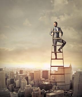 Empresario en la cima de una escalera