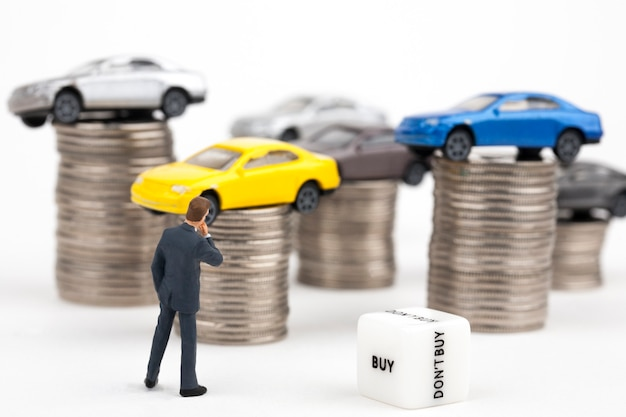 Empresario y coche encima de pila de monedas