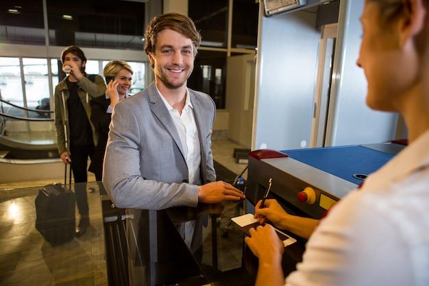 Empresario en cola recibiendo pasaporte y tarjeta de embarque