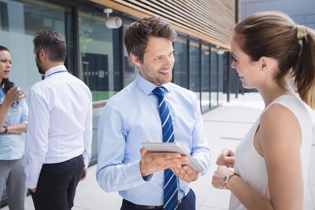 Empresario y colega discutiendo sobre tableta digital