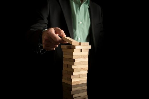 Empresario colocando un bloque de madera en una torre
