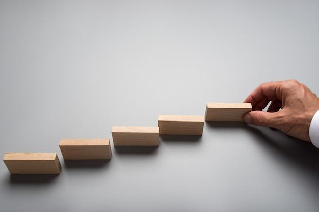 Empresario colocando clavijas de madera o dominó en superficie gris