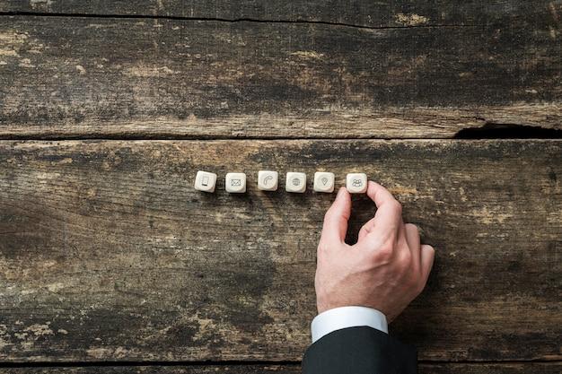 Empresario colocando seis dados de madera con iconos de contacto y comunicación sobre un fondo de madera rústica.