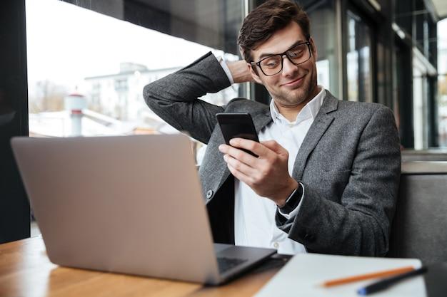 Empresario complacido en anteojos sentado junto a la mesa en la cafetería con computadora portátil mientras usa el teléfono inteligente