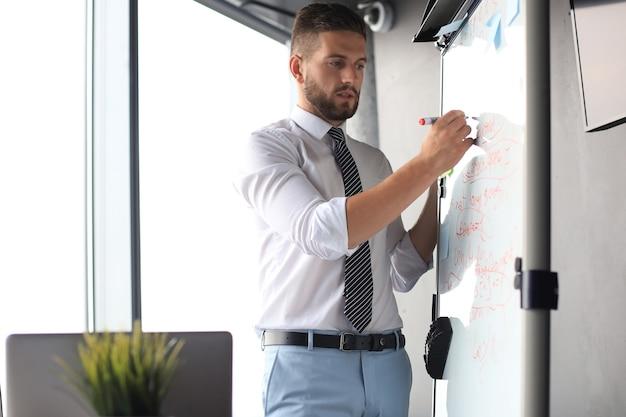 Empresario concentrado inteligente escribiendo algo en el rotafolio con marcador.