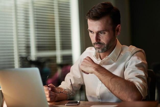 Empresario concentrado usando una computadora portátil en la noche