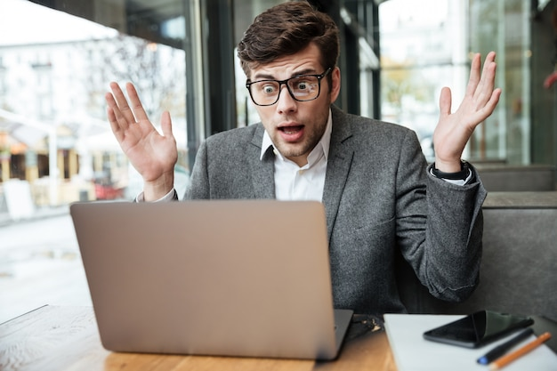 Empresario confundido en anteojos sentado junto a la mesa en la cafetería y mirando la computadora portátil