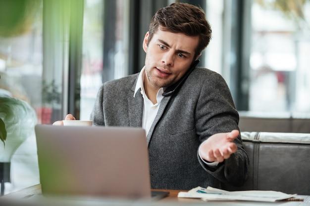 Empresario confundido sentado en la mesa de café con computadora portátil mientras habla por teléfono inteligente