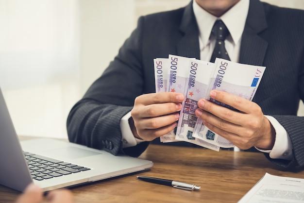 Empresario contando dinero, billetes en euros, en su mesa de trabajo