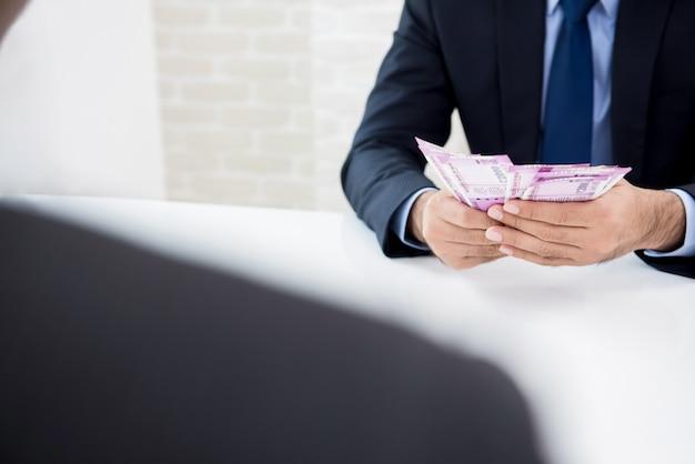 Empresario contando dinero, moneda de la rupia india, recién recibido de su compañero