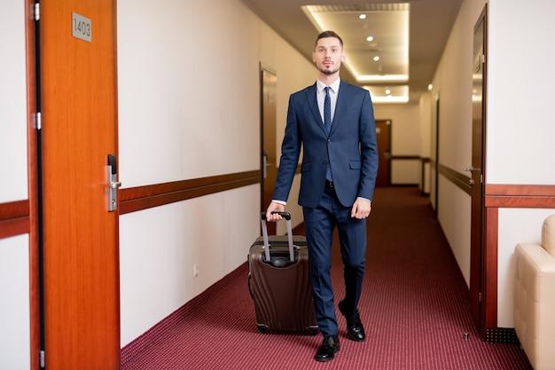 Empresario contemporáneo bien vestido tirando de la maleta con equipaje mientras se mueve hacia su habitación en el hotel