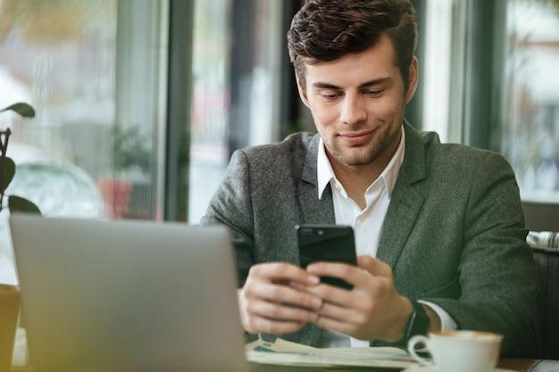 Empresario contento sentado junto a la mesa en la cafetería con computadora portátil mientras usa el teléfono inteligente