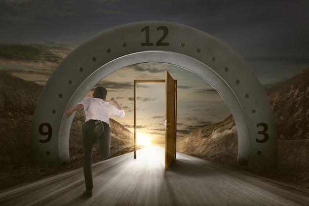Empresario corriendo para abrir la puerta debajo del arco de entrada