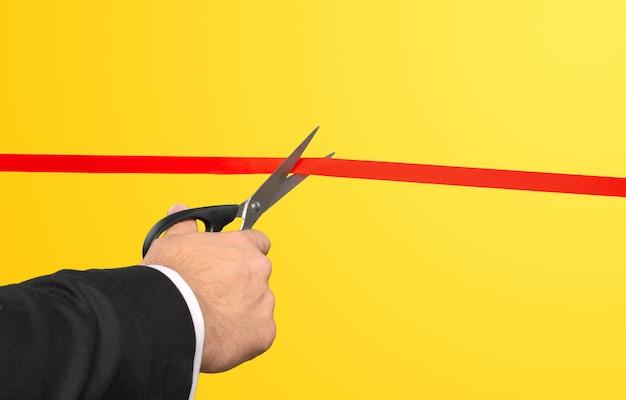 Empresario cortando la cinta roja con unas tijeras