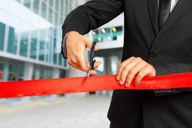 Empresario cortar cinta roja con par de tijeras