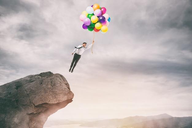 Empresario creativo sosteniendo globos de colores vuela desde la cima de una montaña