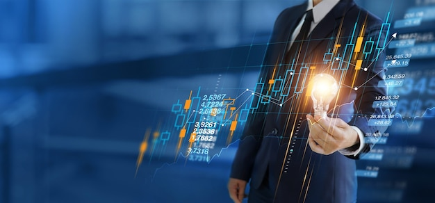 Empresario de crecimiento empresarial sosteniendo bombillas con gráfico de mercado de valores en el cliente de la red global