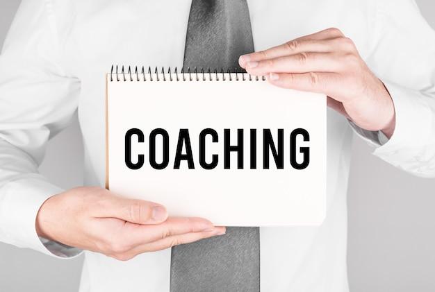 Empresario con cuaderno con texto coaching
