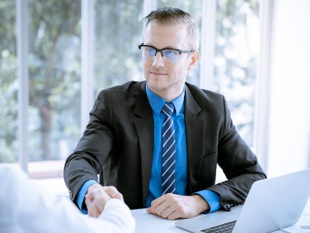 El empresario da la mano a un acuerdo de ventas de lotes grandes que terminan el objetivo de los planes de marketing