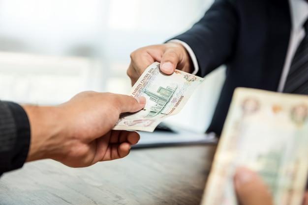 Empresario dando dinero dirham de emiratos árabes unidos