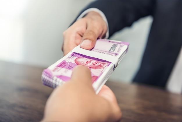 Empresario dando dinero, moneda de la rupia india, a su compañero.