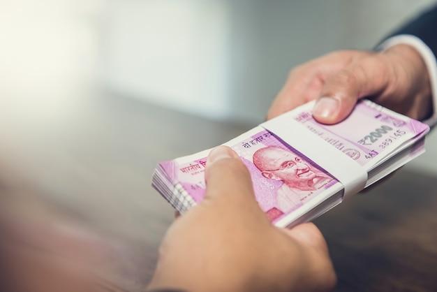 Empresario dando dinero, moneda de la rupia india, a su compañero