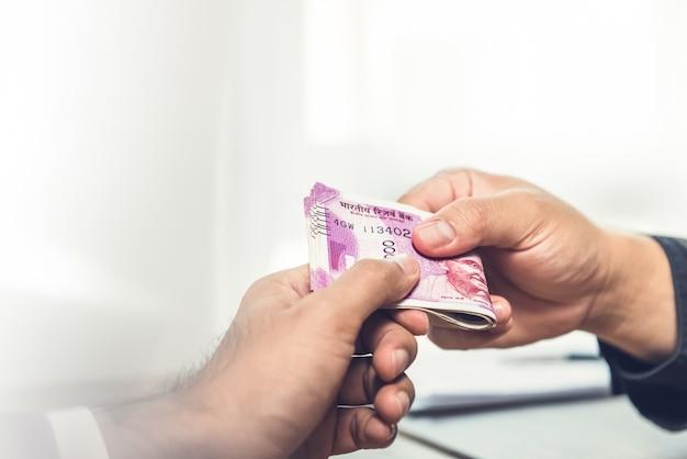 Empresario dando dinero, moneda de la rupia india, a su socio.
